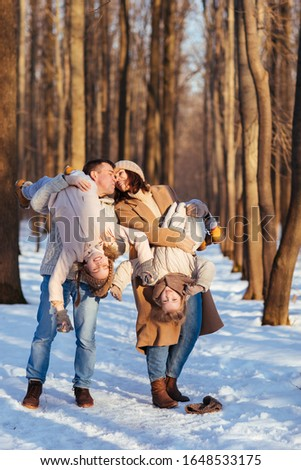 Parents, mom and dad play with her two daughters in the snowy forest. turned upside down, upside down. #1648533175