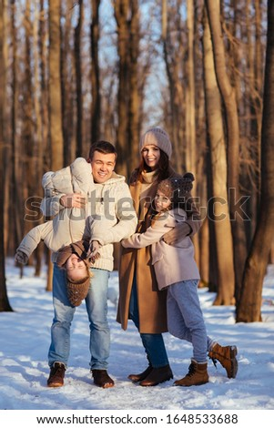 Parents, mom and dad play with her two daughters in the snowy forest. turned upside down, upside down. #1648533688