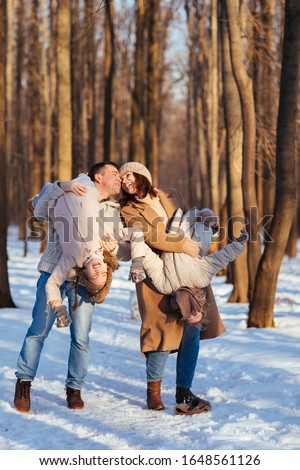 Parents, mom and dad play with her two daughters in the snowy forest. turned upside down, upside down. #1648561126
