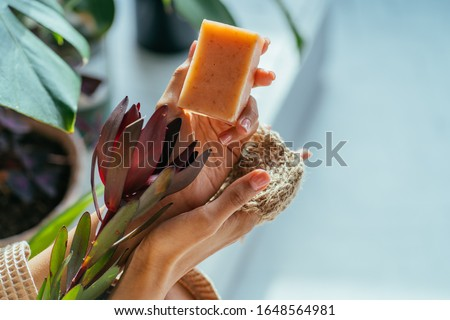 Woman hands holding flower and natural organic solid green soap bar made with olive oil on bath interior green plants background. Healthy lifestyle, beauty,skin care. Zero waste home concept. Royalty-Free Stock Photo #1648564981