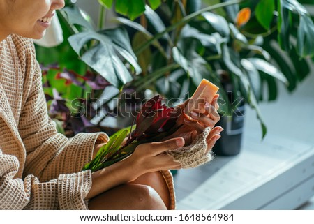 Young woman enjoying morning routine in bathrrom. Eco-friendly cleaning kit. Organic soap and jute washcloth in the woman's hand. Zero waste concept, plastic-free, eco-friendly shopping, vegan #1648564984
