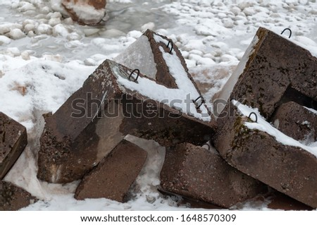 Bank protection - concrete breakwaters on the shore of Lake Ladoga on a cloudy winter day #1648570309