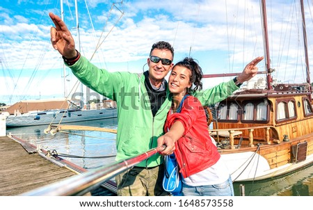 Young couple of lover taking selfie at sailboat docks on tour around world - Love concept  with happy boyfriend and girlfriend at honeymoon cruise on luxury boat experience - Bright vivid filter