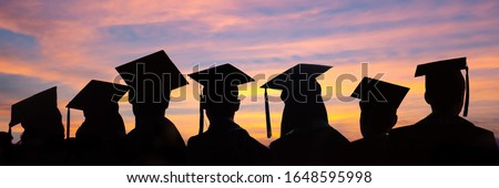 Silhouettes of students with graduate caps in a row on sunset background. Graduation ceremony at university web banner. Royalty-Free Stock Photo #1648595998