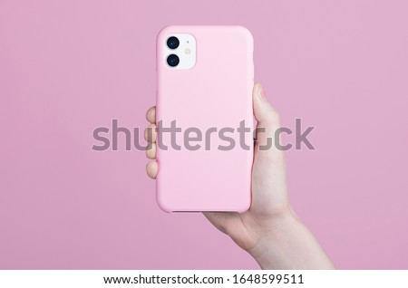 Female hand holding white iPhone 11 in soft silicone pink cover back view. Phone case mock up
