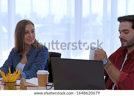Caucasian man and Caucasian young woman are working at the coworking space.They are communicating together with happy mood. The room has white background. Top half of body composition. #1648620679