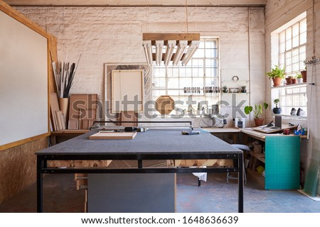 Interior of a manufacturing area of a picture framing studio with a variety of tools and different sized wooden frames Royalty-Free Stock Photo #1648636639