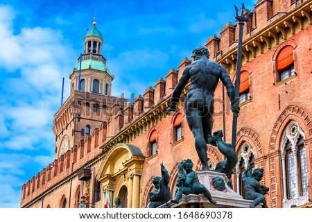 The Fountain of Neptune (Fontana di Nettuno) with Palazzo d'Accursio in background in Bologna, Italy. Architecture and landmark of Bologna. Cityscape of Bologna.