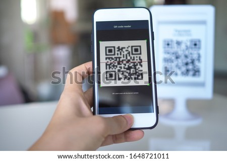 Women's hand uses a mobile phone application to scan QR codes in stores that accept digital payments without money and plastic tags on the table. QR code payment and cash technology concept #1648721011