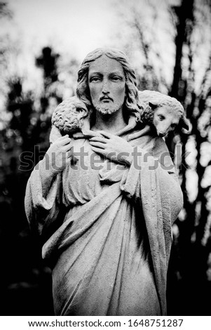 Dramatic white and black image with deep shadows. Antique statue of Jesus Christ Good Shepherd
