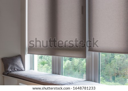 Motorized roller shades. Automatic roller blinds beige color on large windows. Remote Control Shades are near the sofa with the pillow. Sofa covered with pastel velours. Summer. Green trees outside. #1648781233