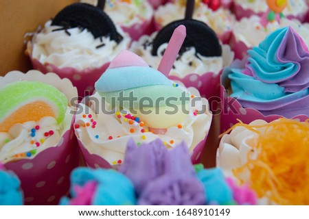 The cup cake a beautiful color in the middle of the picture and there are blurry images of the various cup cakes around.