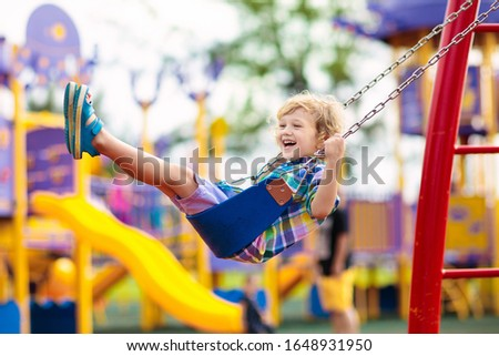 Child on swing playing on outdoor playground. Kids play on school or kindergarten yard. Active kid swinging. Healthy summer activity for children. Little boy having fun outdoors. #1648931950
