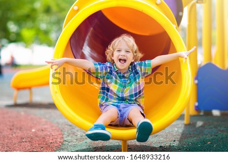 Child playing on outdoor playground. Kids play on school or kindergarten yard. Active kid on colorful slide and swing. Healthy summer activity for children. Little boy climbing outdoors. #1648933216
