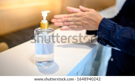 Washing hands by alcohol sanitizers or alcohol gel from pump bottle in public area. Wuhan coronavirus (COVID-19) outbreak infection prevention and control. Hygiene and health care concept #1648940242
