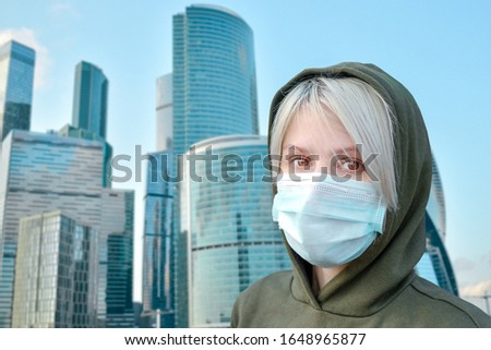 girl in a medical mask on a background of the city. The fight against the epidemic. Personal protective equipment. Disposable medical three-layer mask with elastic.