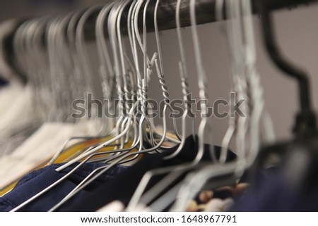 clothes hanger closeup of fashion shop. aluminium hanger with clothes. clothes in a cloakroom. Clothing of women's shirts on hangers at clothing store #1648967791