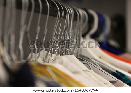 clothes hanger closeup of fashion shop. aluminium hanger with clothes. clothes in a cloakroom. Clothing of women's shirts on hangers at clothing store #1648967794