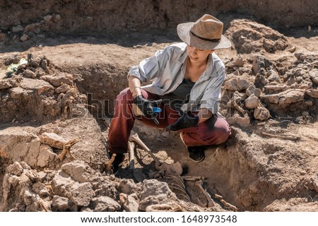 Archaeological excavations. Young archaeologist excavating part of human skeleton and skull from the ground.  Royalty-Free Stock Photo #1648973548