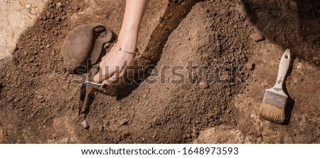 Archaeologist digging with hand trowel, recovering ancient pottery object from an archaeological site. Royalty-Free Stock Photo #1648973593