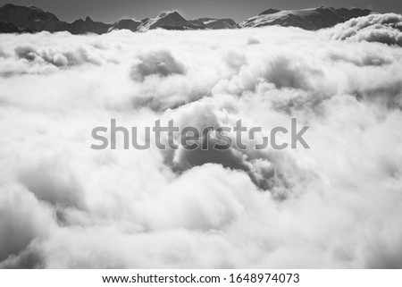 Photo taken in the french Alps in cloudy and windy conditions, which set a ferric atmosphere, with mountains emerging from the clouds, sea of clouds, forests, trees, black and white. #1648974073