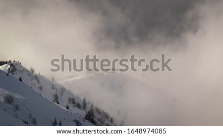 Photo taken in the french Alps in cloudy and windy conditions, which set a ferric atmosphere, with mountains emerging from the clouds, sea of clouds, forests, trees, black and white. #1648974085