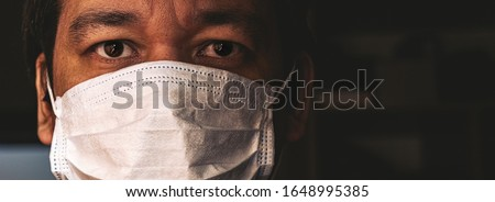 Closeup of man in mask, concept of viral infection. Theme of corona-virus epidemic. Royalty-Free Stock Photo #1648995385