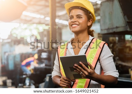 Industry maintenance engineer woman dark skin wearing uniform and safety helmet under inspection and checking production process on factory station by tablet. Industry, Engineer, construction concept. #1649021452