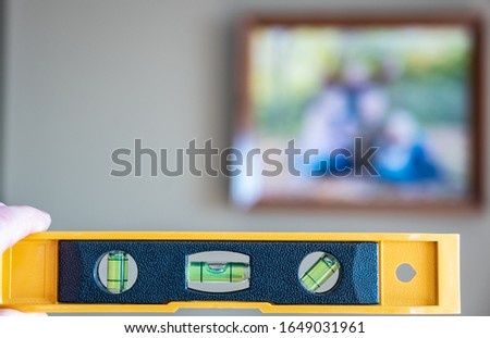 Hand holding bubble level in front of a blurred picture frame in the background