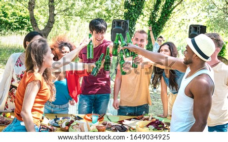 Happy multiracial friends toasting beer at barbecue garden party - Friendship concept with people having fun at backyard summer camp - Food and drinks dinner moment with dj music set - Warm filter