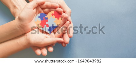 Adult and child hands holding jigsaw puzzle heart shape, Autism disorder awareness, Autism spectrum family support concept, World Autism Awareness Day #1649043982