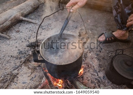Cooking on fire. Man Cook Some Food in Bowler Camp #1649059540