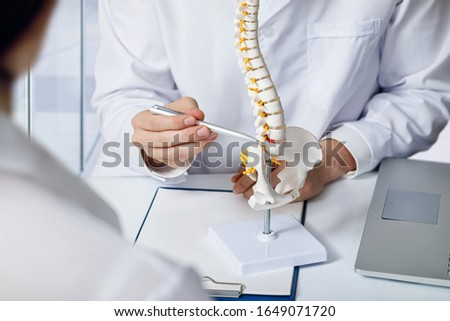 The doctor shows an intervertebral hernia on the spine at the table.