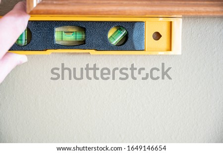 Hand holding bubble level against picture frame to check angle