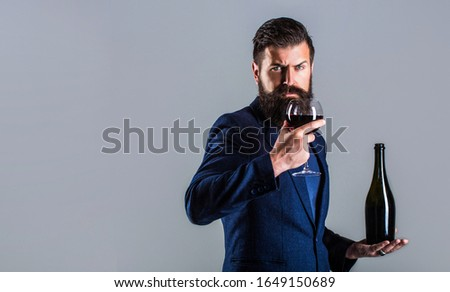 Red wine in bottle, wine glass. Sommelier man, degustator, winery. Man holding bottle with champagne, wine. Bottle, red wine glass. Beard man, bearded, sommelier, tasting. #1649150689