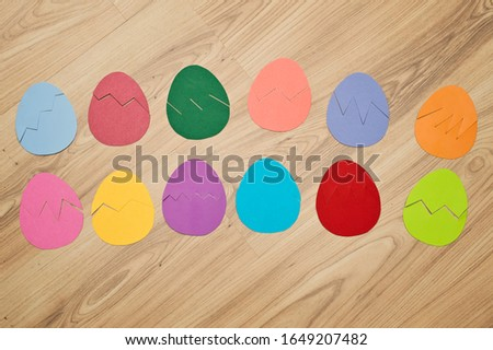 Different color paper eggs on the floor. Easter theme game, find other side of figure. boy playing on the floor.