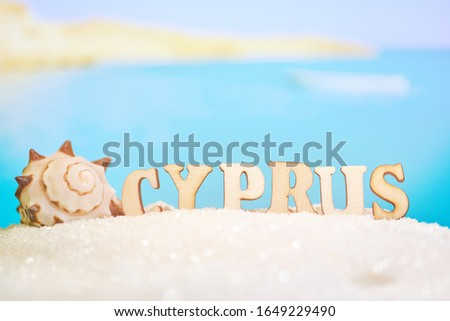 Abstract beach sand seashell on a blurred sea background with boat and letters. Cyprus is one of the most popular resorts in the world. Close up.