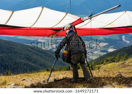 Paraglider about to launch at the top of the hill, Creston, British Columbia, Canada. Kootenay valley mountains in the background #1649272171