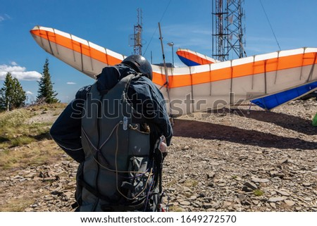 A young extremal guy preparing and double-checking his special equipment and gears for a Hang gliding fly. View from the behind #1649272570