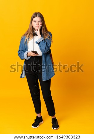 Student ukrainian teenager girl over isolated yellow background unhappy and frustrated #1649303323