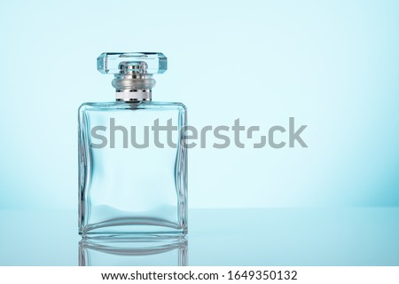 Perfume glass bottle. Clear parfum glass bottle with spray atomizer. Blue background. Copy space and mockup.