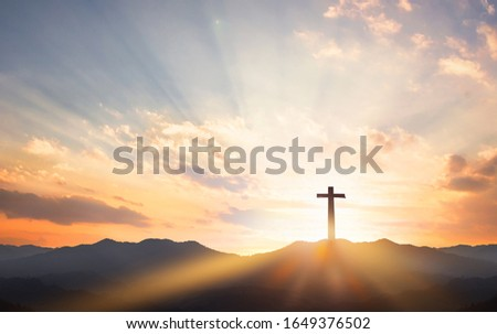 Good Friday concept: cross with sunset in the sky background
