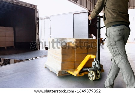 Cargo shipment loading for truck. Worker courier unloading cargo pallet shipment goods, package box, his using hand pallet  jack load into a truck, Road freight truck transportation.  Royalty-Free Stock Photo #1649379352