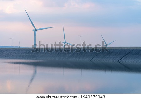 wind turbine generating electricity on dam catchment landscape energy transmission distribution equipment in natural environment. #1649379943