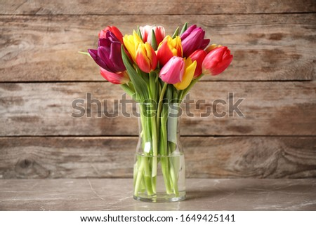 Beautiful spring tulips in vase on table against wooden background #1649425141