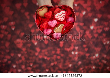 heart-shaped box, with heart-shaped jelly beans, heart-shaped cookies and red background #1649524372