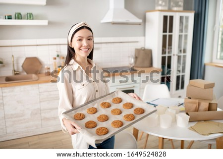 Work and hobbies. Successful happy woman with a tray of home baking, standing near the table with paper packages.
