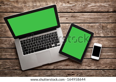 Open laptop with digital tablet and white smartphone. All with isolated screen on old wooden desk. Royalty-Free Stock Photo #164958644