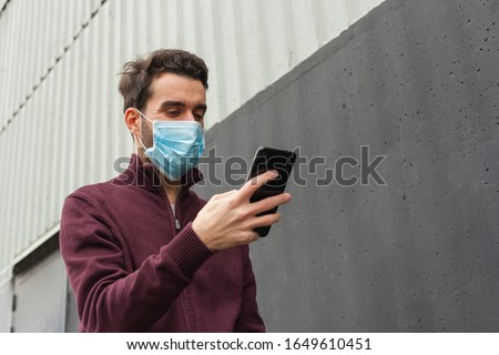 White bearded adult man using smartphone while wearing surgical mask on an industrial wall. Health, epidemics, social media, communication and lifestyle stills with copy space. #1649610451