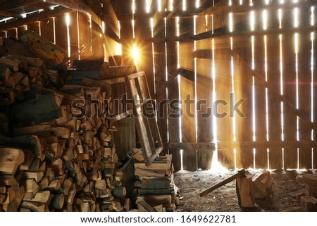 Firewood stored in the old barn. Sun shining  in an old barn. Beautiful retro vintage coceptual photo.